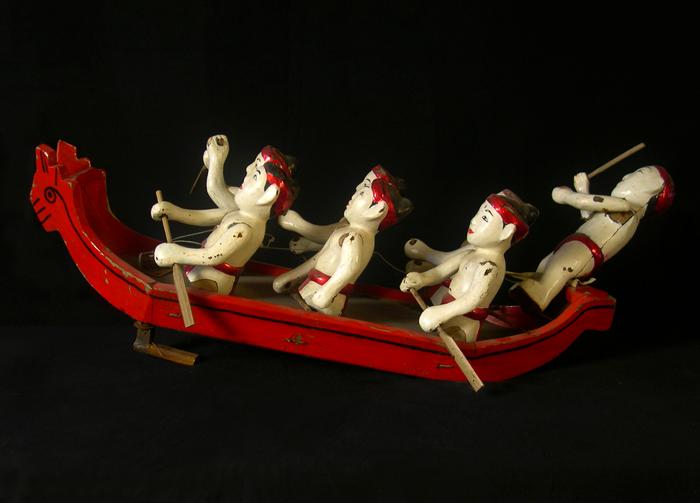Sept hommes sur une barque rouge, marionnette sur eau.