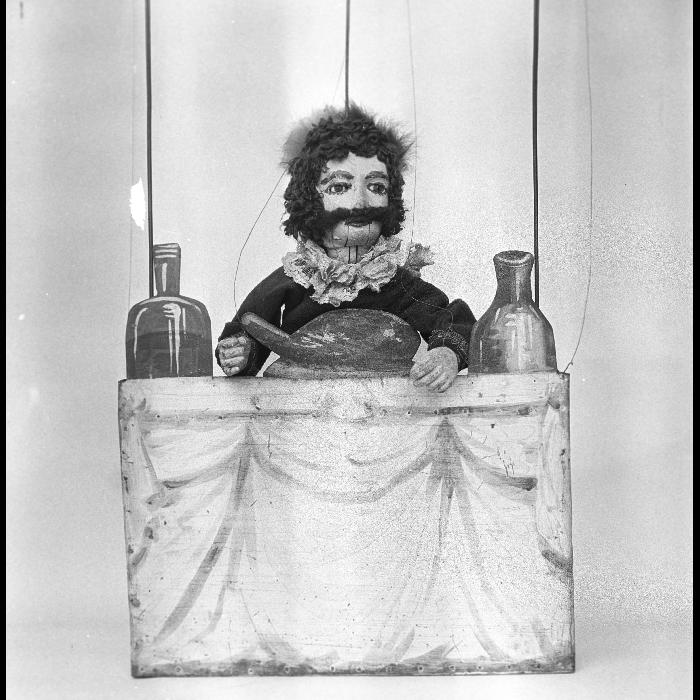 Fantoches perfectionnés. L'ogre à sa table se métamorphose en lion devant le chat botté. La tête de l'ogre sert pour le mystère de la Passion dans le rôle de Jésus-Christ. Théâtre forain de Monsieur et Madame Dulaar.